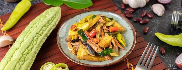 Caranguejo frito com curry em pó em um prato com pimentão e tomate.