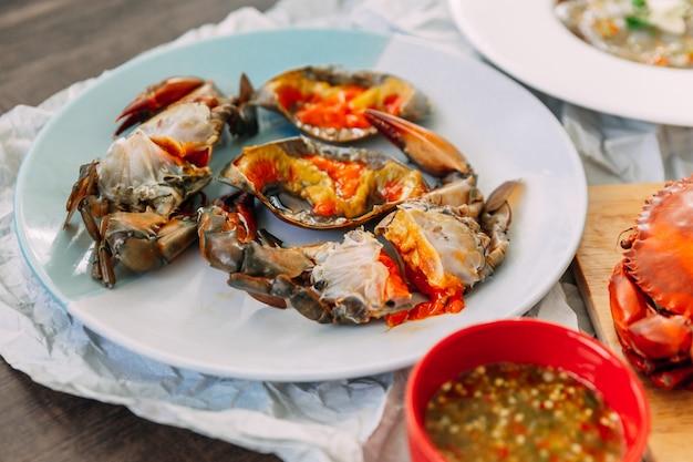 Caranguejo marinado com molho de peixe e ovos de caranguejo em conserva servidos com molho de marisco picante de estilo tailandês.