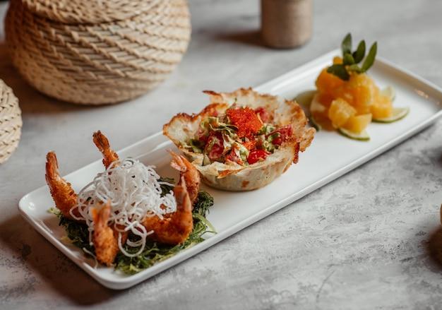 Caranguejos grelhados com canapé de pão recheado com salada verde e fatias de abacaxi