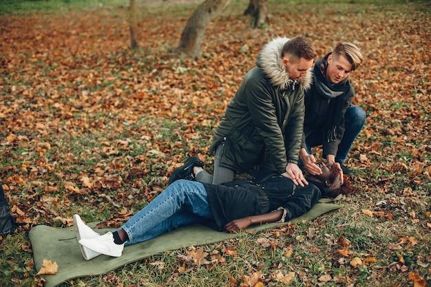 Caras ajudam uma mulher. garota africana está deitada inconsciente. prestando primeiros socorros no parque.