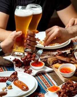 Caras bebe cerveja com vários petiscos