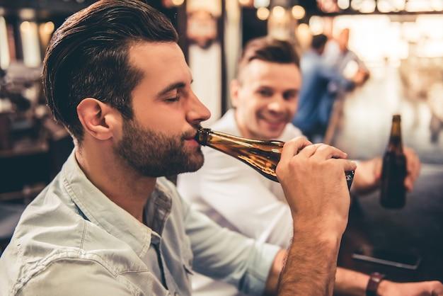 Caras bonitos estão bebendo cerveja no bar.