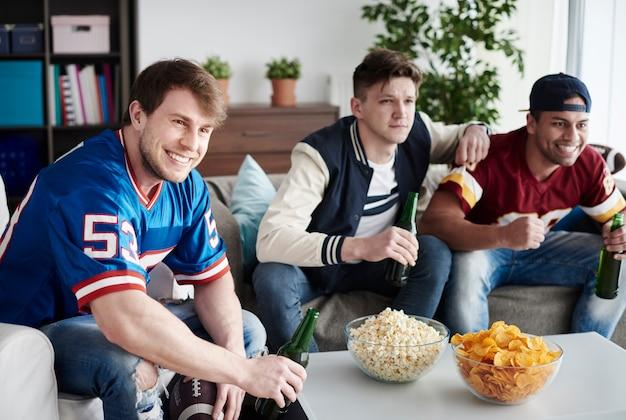Caras comemorando partida de futebol em casa