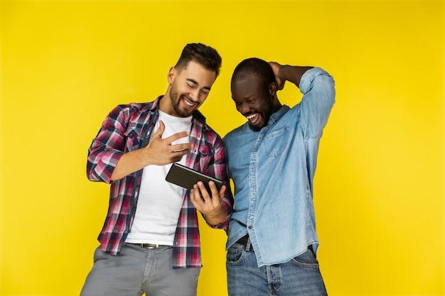 Caras europeus e afro-americanos estão olhando para o tablet e rindo