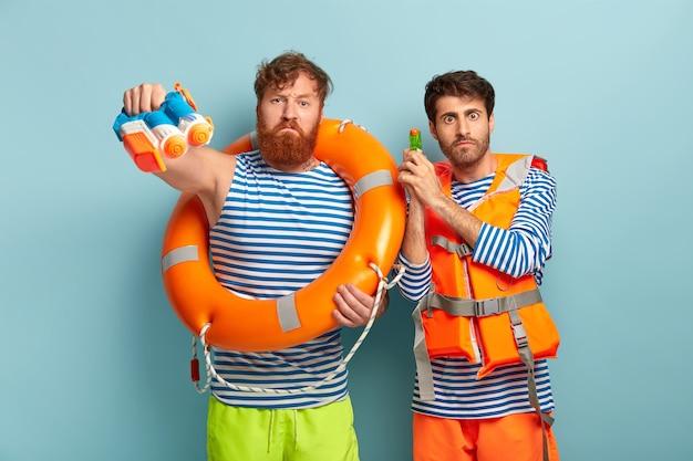 Caras posando na praia com colete salva-vidas e bóia salva-vidas
