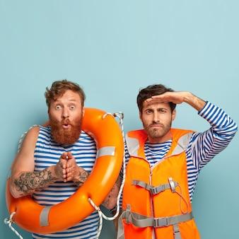 Caras surpresos posando na praia com colete salva-vidas e bóia salva-vidas