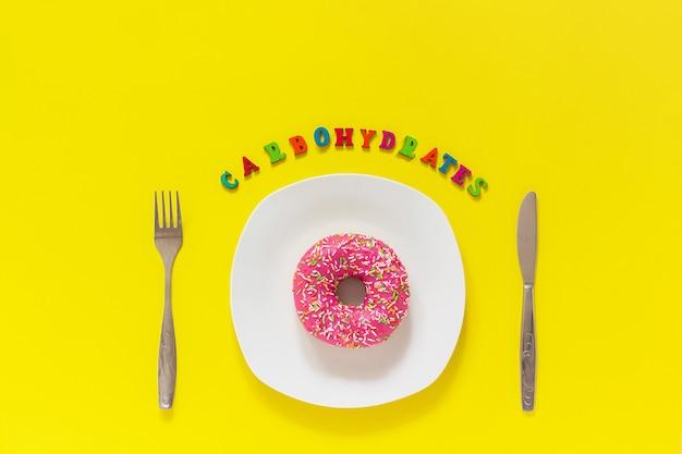 Carboidratos de texto, donut rosa na placa e garfo de faca de mesa de talheres dieta insalubre
