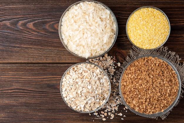 Carboidratos. vários flocos de grãos em tigelas na mesa de madeira escura.