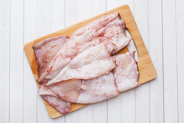 Carcaça crua do calamar com as especiarias e o limão prontos para cozinhar na tabela.