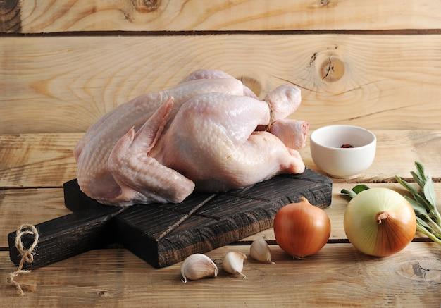 Carcaça de frango cru inteiro no tabuleiro e especiarias