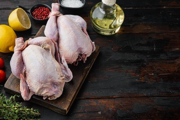 Carcaça de frango inteiro cru fresco com ingredientes, na velha mesa de madeira com espaço de cópia para o texto
