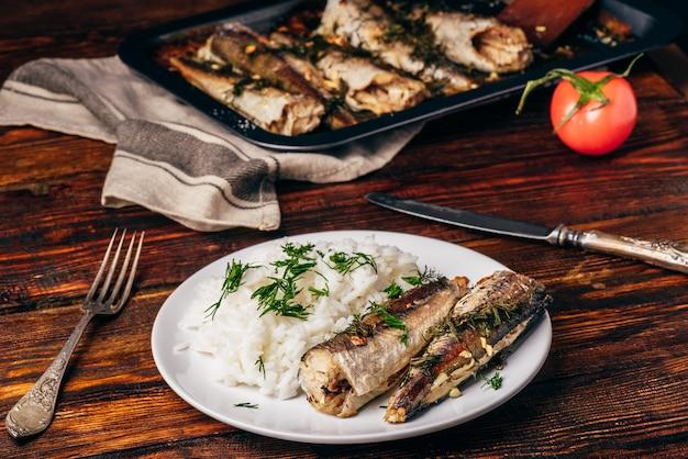 Carcaças de pescada assada com arroz no prato branco