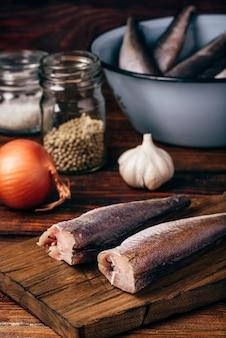 Carcaças de pescada na tábua de cortar com pimenta, alho e sal