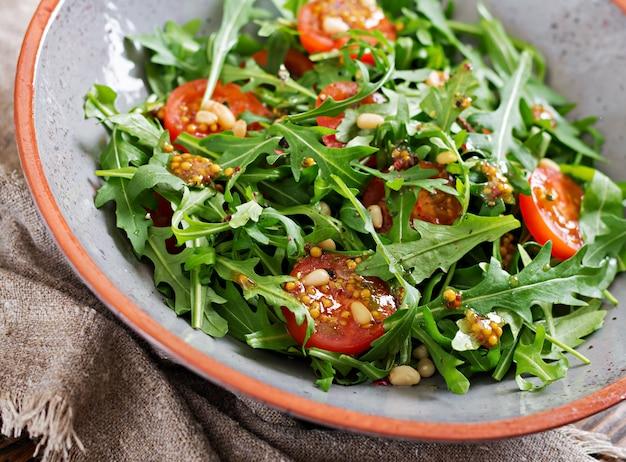 Cardápio dietético. cozinha vegana. salada saudável com rúcula, tomate e pinhões.
