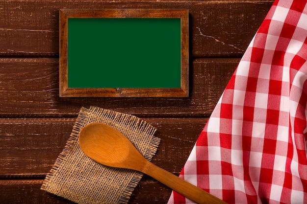 Cardápio do restaurante. vista superior do menu de quadro-negro deitado sobre a mesa de madeira rústica com colheres e guardanapo vermelho. vista superior.