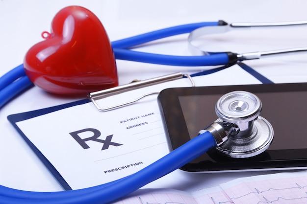 Cardiogram com estetoscópio e coração vermelho na mesa