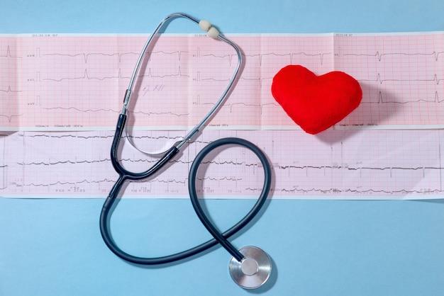 Cardiograma com estetoscópio médico e coração vermelho em uma mesa azul, close-up