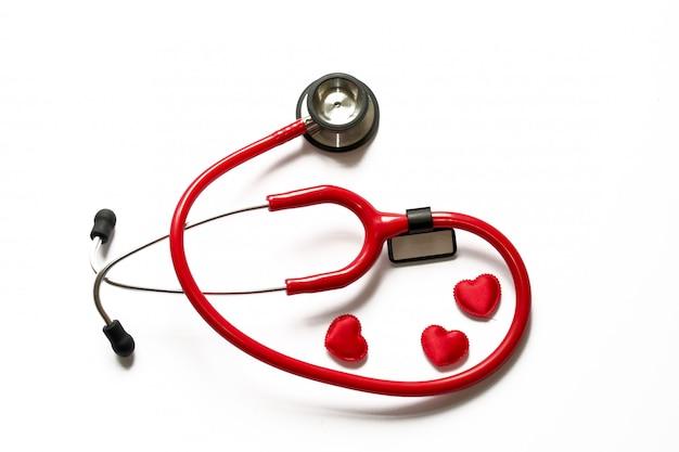 Cardiologia. estetoscópio e coração vermelhos ascendentes próximos da medicina isolados no fundo. copie espaço