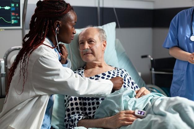 Cardiologista afro-americano examinando o coração do paciente sênior