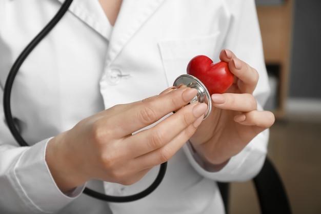 Cardiologista com coração vermelho e estetoscópio na clínica