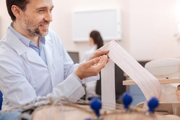 Cardiologista competente e sorridente explicando ao paciente os resultados de seu eletrocardiograma após examiná-lo cuidadosamente de antemão