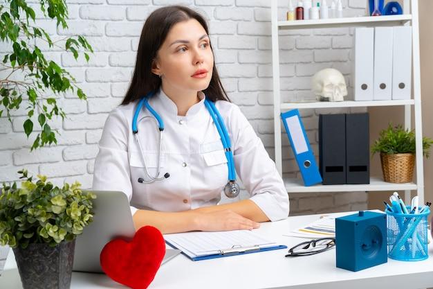 Cardiologista jovem médico feminino sentado em sua mesa e trabalhando