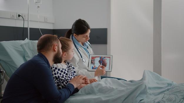 Cardiologista pediátrica, médica, explicando doença cardíaca usando tablet com eletrocardiograma médico