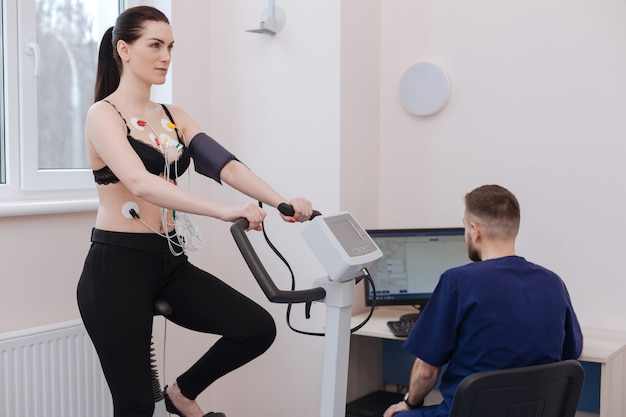 Cardiologista profissional competente e ocupado conduzindo um procedimento de diagnóstico examinando o nível de pressão arterial e frequência cardíaca de pacientes