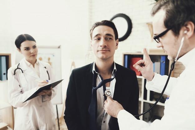 Cardiologista qualificado ouvindo o batimento cardíaco do paciente.