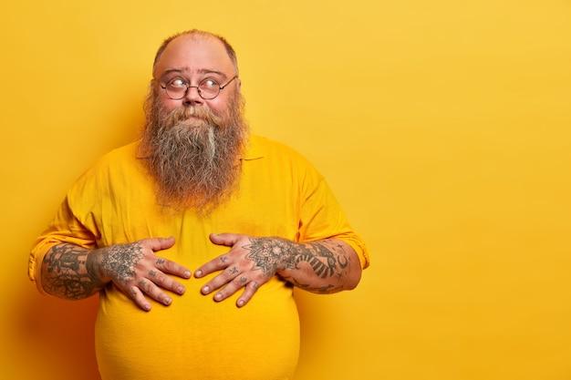 Careca barbudo pensativo mantém as mãos na barriga grande, fica em pose pensativa, tem braços tatuados, barba espessa, usa óculos redondos, isolado sobre parede amarela, espaço em branco à parte, pensa ou duvida
