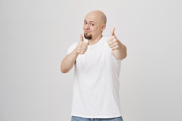 Careca bonito sorrindo, mostrando o polegar para cima em aprovação