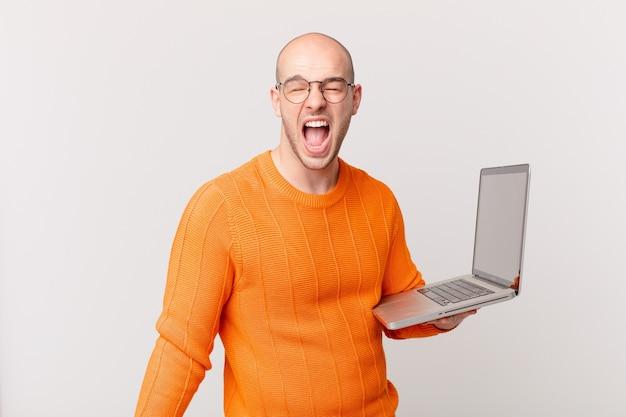 Careca com computador gritando agressivamente, parecendo muito zangado, frustrado, indignado ou irritado, gritando não