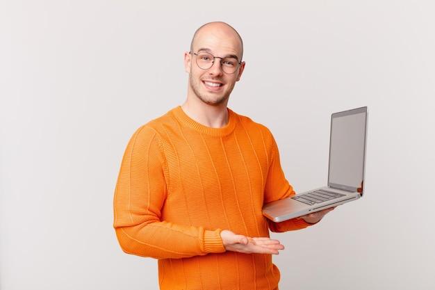 Careca com computador sorrindo alegremente, sentindo-se feliz e mostrando um conceito no espaço da cópia com a palma da mão