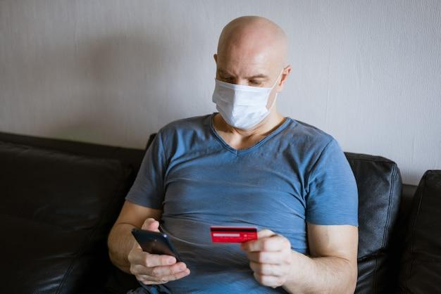 Careca com máscara protetora e telefone