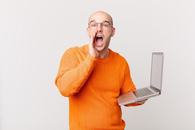 Careca com o computador se sentindo feliz, animado e positivo, dando um grande grito com as mãos perto da boca, gritando