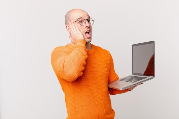 Careca com o computador se sentindo feliz, animado e surpreso, olhando para o lado com as duas mãos no rosto
