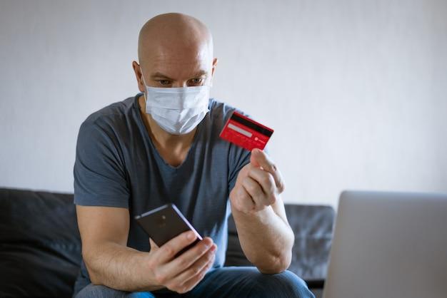 Careca com uma máscara médica e um cartão de crédito sentado no sofá em um laptop com um telefone