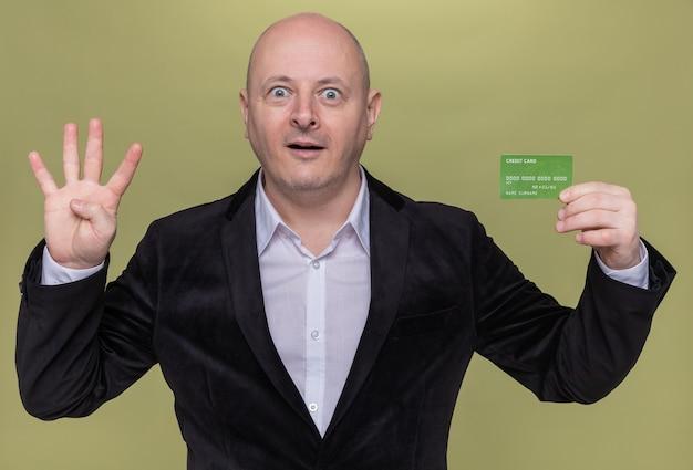 Careca de meia-idade de terno segurando um cartão de crédito, olhando para a frente, sorrindo e surpreso, mostrando o número quatro com os dedos em pé sobre a parede verde
