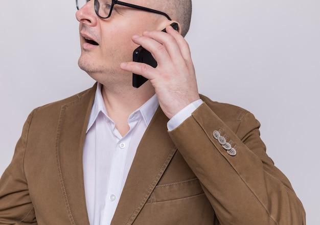 Careca de meia-idade em um terno de óculos, sorrindo feliz e positivo enquanto fala no celular