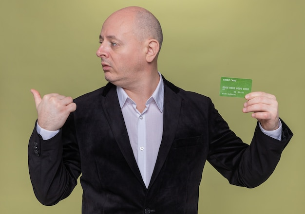 Careca de meia-idade em um terno segurando um cartão de crédito, olhando para o lado, apontando para trás com um polegar em pé sobre uma parede verde