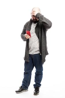Careca de óculos com um telefone nas mãos. altura toda. isolado sobre a parede branca. vertical.
