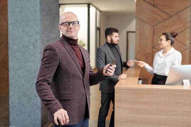 Careca elegante, homem maduro, empresário jovem em pé no lounge do hotel