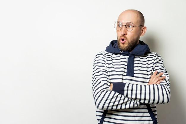 Careca jovem com uma barba em copos de uma jaqueta com capuz parece longe com um rosto surpreso em um branco isolado. gesto de choque, surpresa