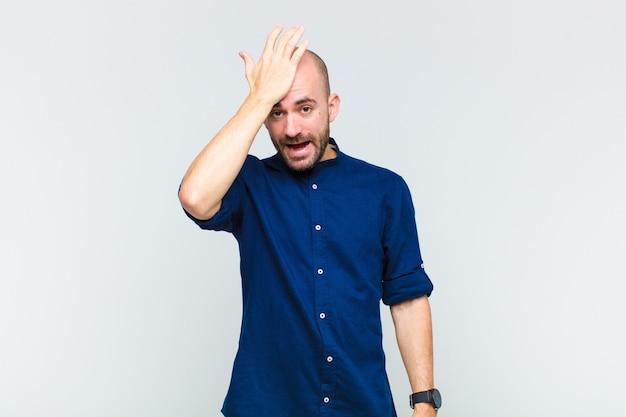 Careca levantando a palma da mão na testa pensando opa, depois de cometer um erro estúpido ou lembrar, sentindo-se burro