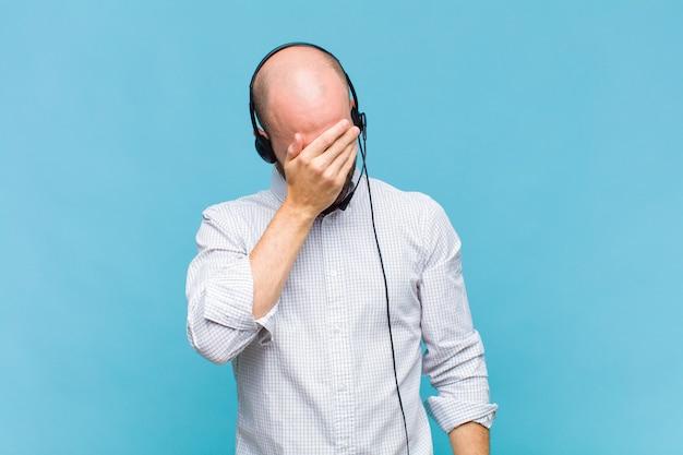 Careca parecendo estressado, envergonhado ou chateado, com dor de cabeça, cobrindo o rosto com a mão