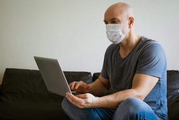 Careca sentado em um laptop com máscara médica e cartão de crédito na mão