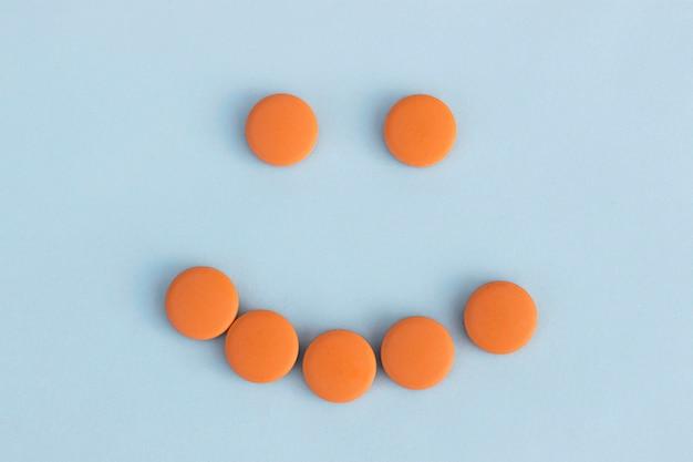 Caretas de comprimidos alaranjados sobre um fundo azul. conceito de antidepressivos