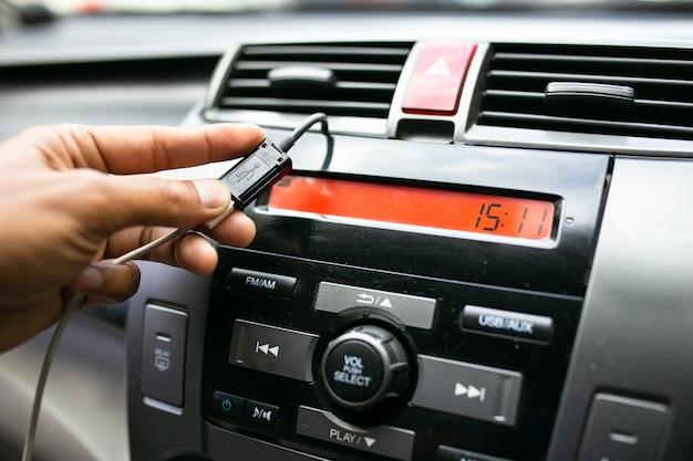 Carga da terra arrendada da mão do homem o telefone esperto móvel da bateria de usb no carro.
