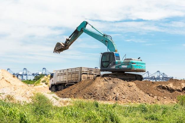 Carga de carro digger e transferência de solo para caminhão na colina, máquina de tecnologia e conceito de transporte