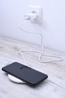 Carga do telefone móvel em um carregador sem fio, conceito de equipamento moderno em uma mesa de madeira